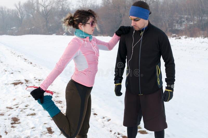 Homem e mulher que aquecem-se antes de parte externa running na neve foto de stock