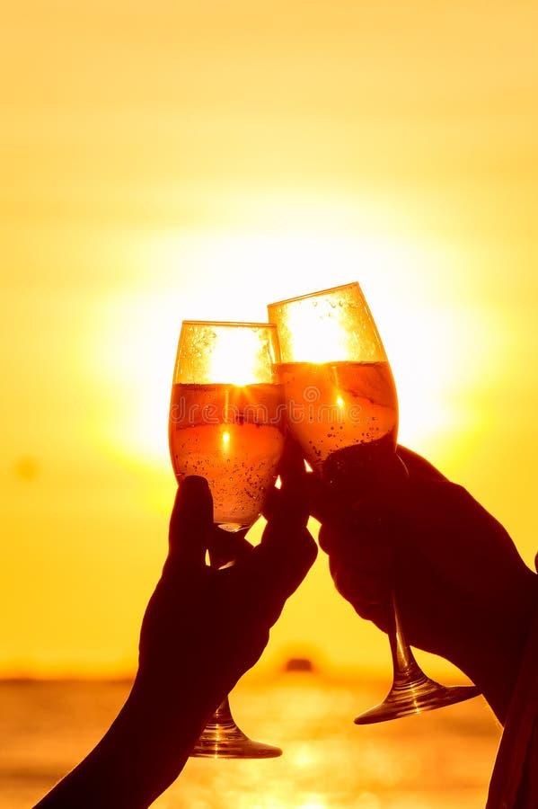 Homem e mulher que clangoram vidros de vinho com champanhe no por do sol imagens de stock royalty free