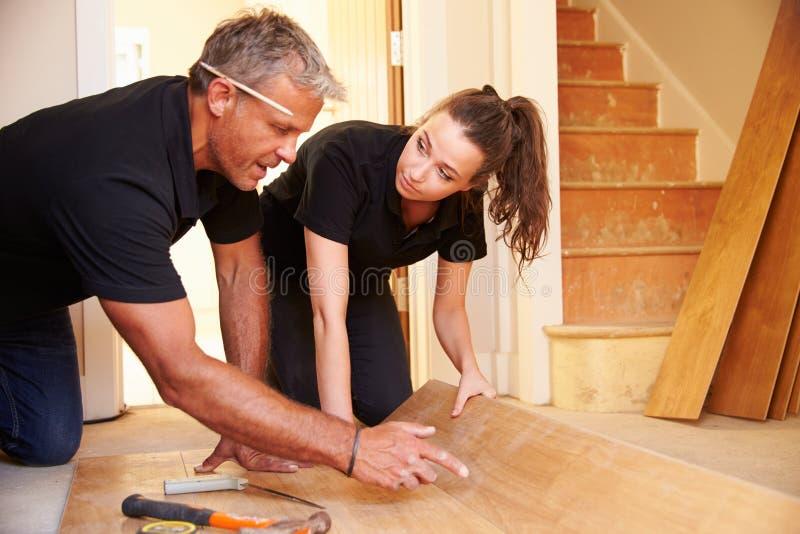 Homem e mulher que colocam o revestimento de madeira do painel em uma casa fotos de stock royalty free