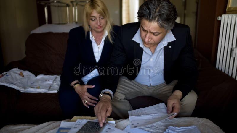 Homem e mulher que contam as despesas, verificando contas para ver se há utilidades, orçamento de família imagens de stock royalty free