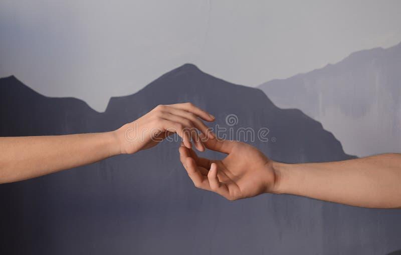 Homem e mulher que dão-se as mãos no fundo cinzento Conceito do apoio e da ajuda imagem de stock