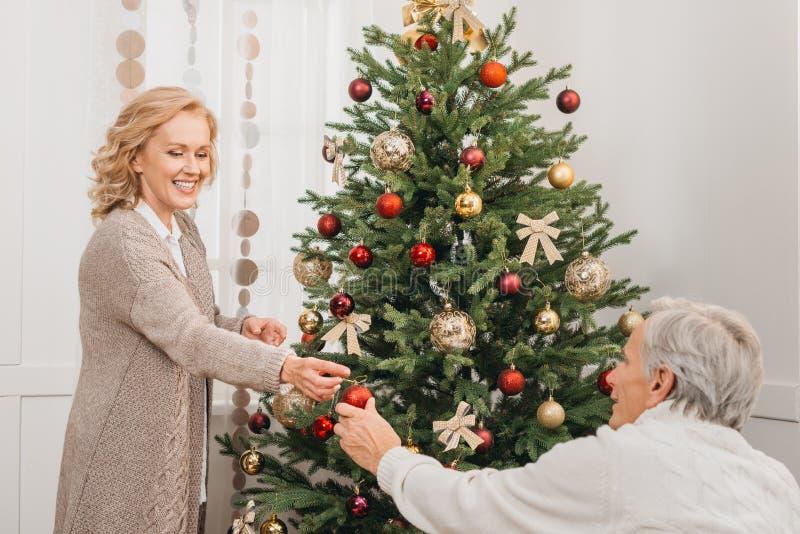Homem e mulher que decoram a árvore de Natal foto de stock