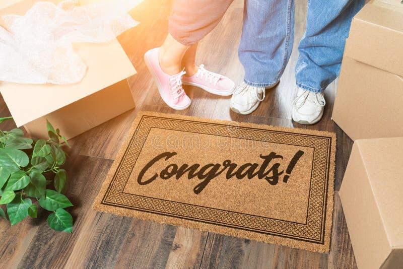 Homem e mulher que desembalam perto da esteira bem-vinda com Congrats, as caixas móveis e a planta fotos de stock royalty free