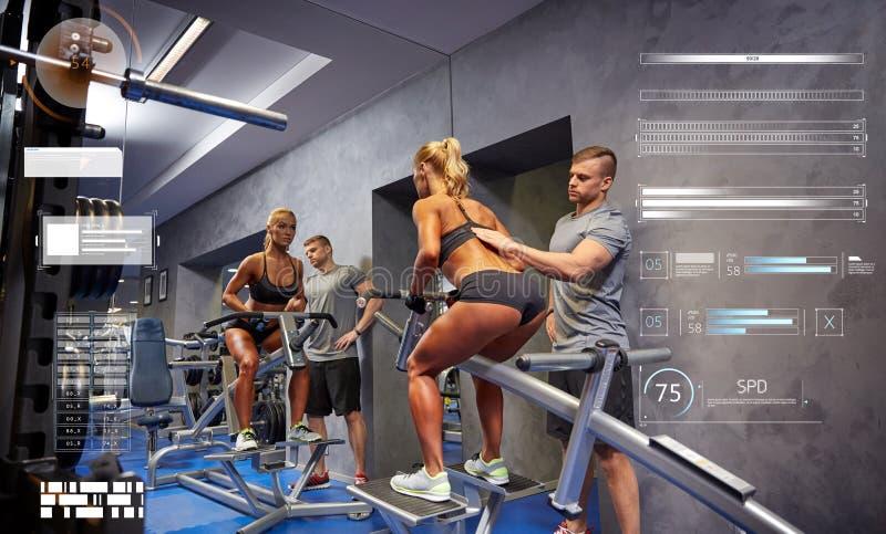 Homem e mulher que dobram os músculos na máquina do gym fotografia de stock
