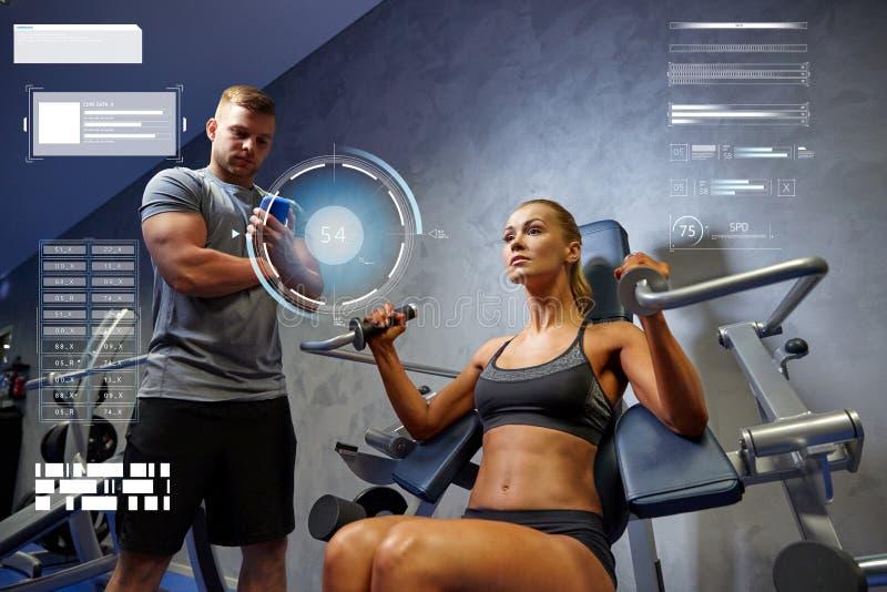 Homem e mulher que dobram os músculos na máquina do gym imagens de stock
