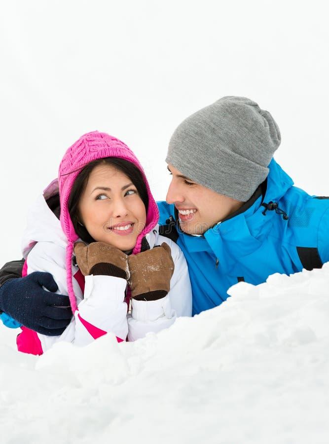 Homem e mulher que encontram-se na neve fotos de stock