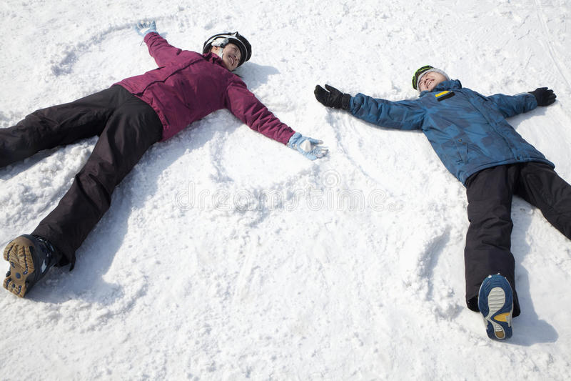 Homem e mulher que encontram-se na neve que faz o anjo da neve foto de stock royalty free