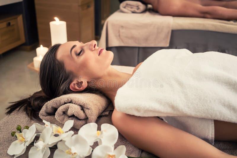 Homem e mulher que encontram-se para baixo em camas da massagem no cente asiático do bem-estar fotos de stock