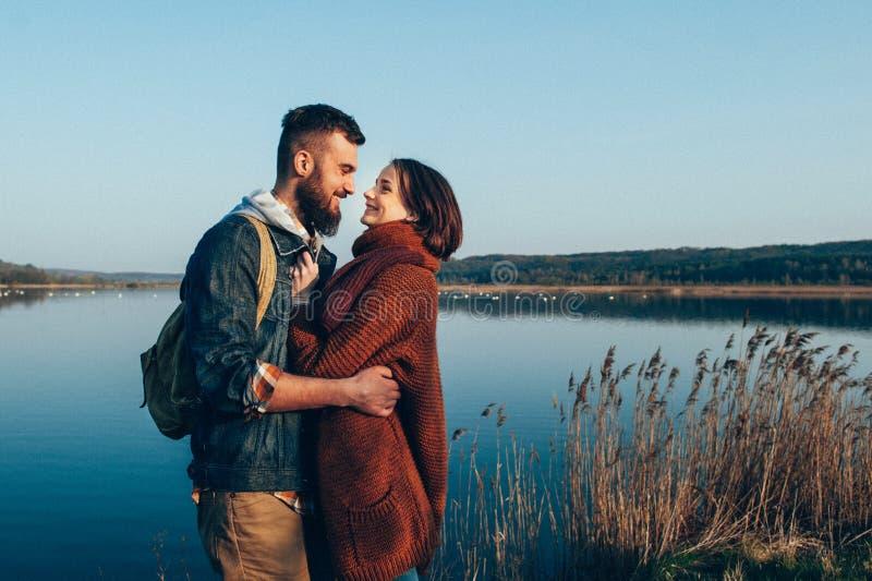Homem e mulher que estão com canoa e pá na costa do lago na manhã ensolarada fotografia de stock