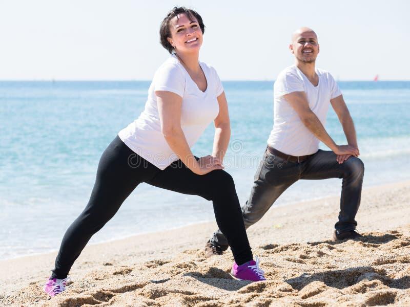 Homem e mulher que exercitam junto na praia fotografia de stock