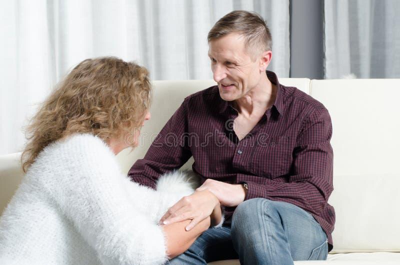 Homem e mulher que falam no sofá imagem de stock
