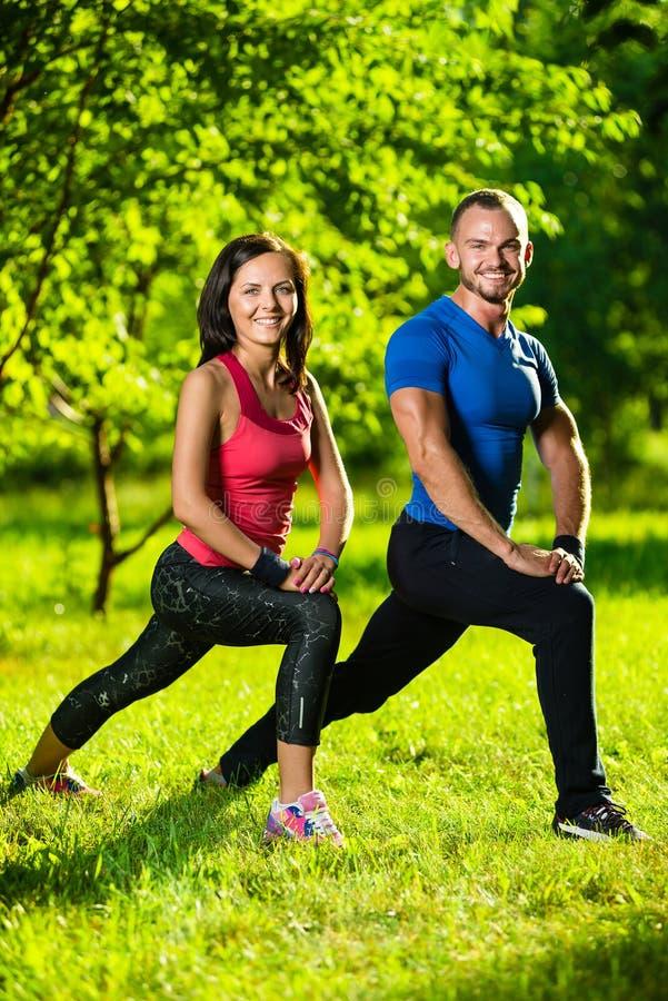 Homem e mulher que fazem esticando exercícios imagens de stock royalty free