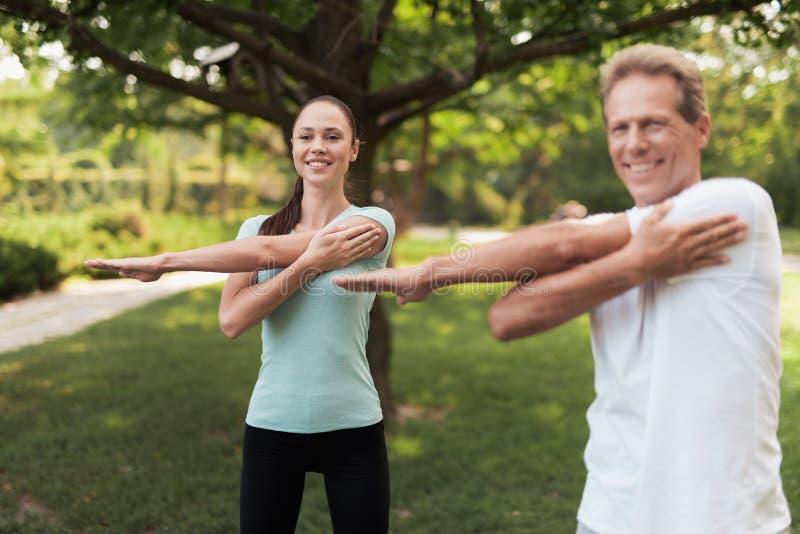Homem e mulher que fazem exercícios no parque Aquecem-se imagens de stock