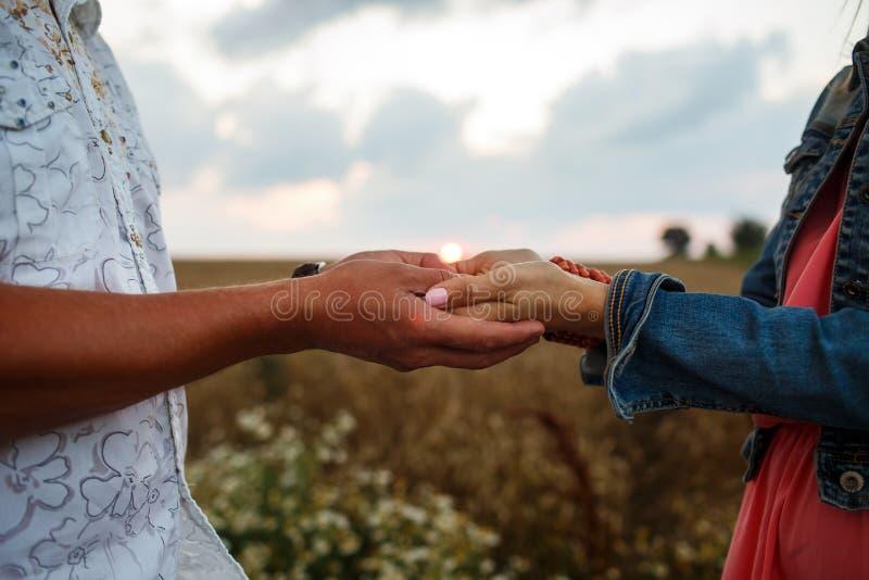 Homem e mulher que guardam as mãos que andam no campo no por do sol fotografia de stock royalty free