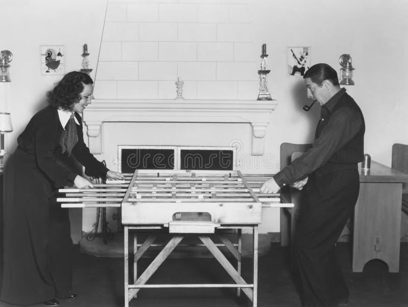 Homem e mulher que jogam o foosball fotografia de stock royalty free