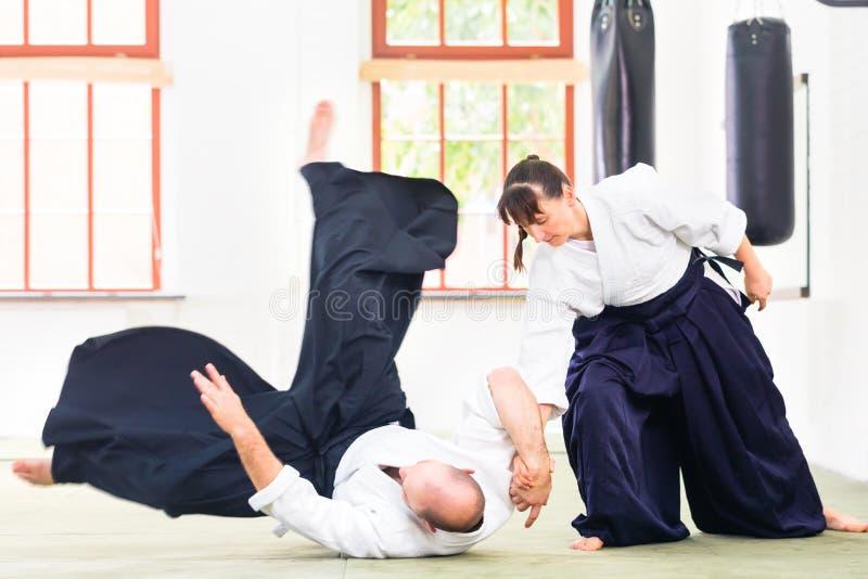Homem e mulher que lutam na escola de artes marciais do Aikido fotografia de stock royalty free