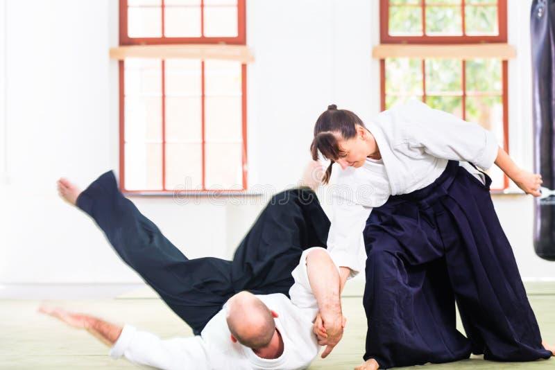 Homem e mulher que lutam na escola de artes marciais do Aikido imagem de stock
