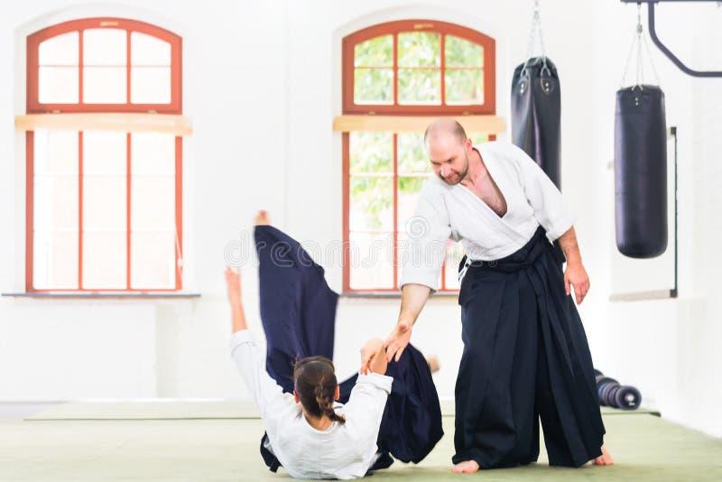 Homem e mulher que lutam na escola de artes marciais do Aikido fotos de stock royalty free