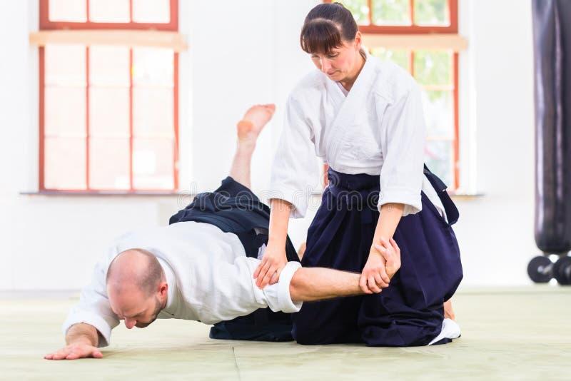 Homem e mulher que lutam na escola de artes marciais do Aikido imagens de stock