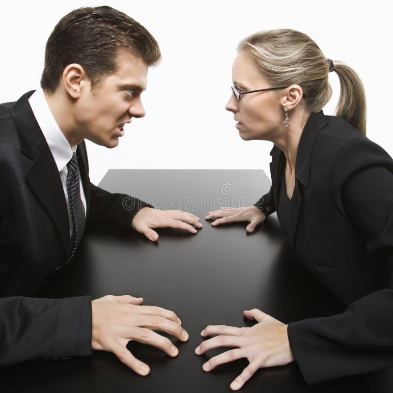 Homem e mulher que olham fixamente em se com expressões hostis. fotos de stock