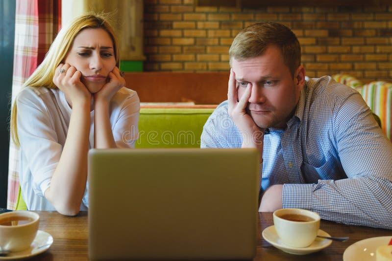 Homem e mulher que olham o portátil São entristecidos e afligidos fotografia de stock royalty free