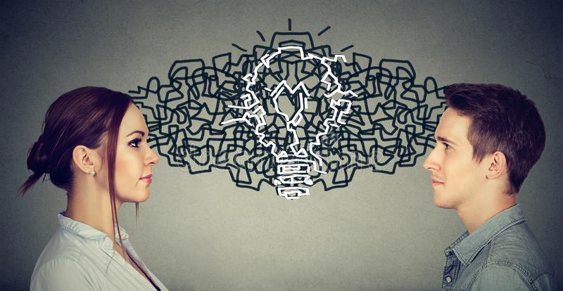Homem e mulher que olham se que troca seus pensamentos que vêm acima junto com uma ampola da ideia imagens de stock