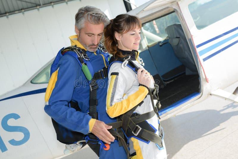 Homem e mulher que preparam-se para o salto de paraquedas em tandem fotografia de stock
