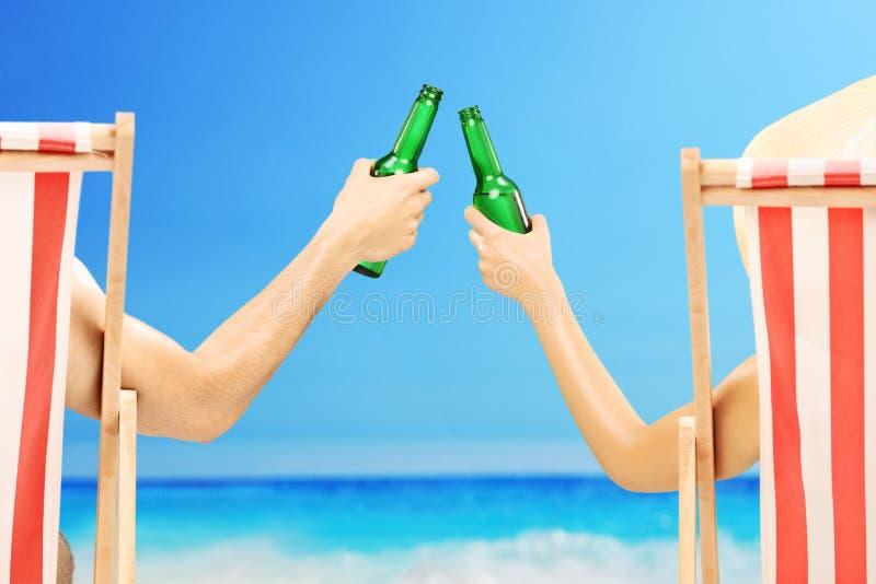 Homem e mulher que relaxam em uma praia e que cheering com cerveja imagens de stock royalty free