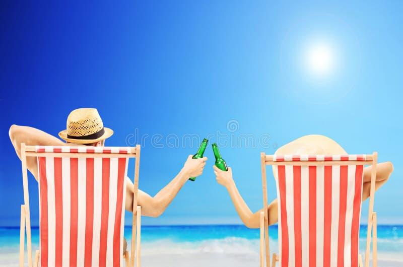 Homem e mulher que relaxam em uma praia e que cheering com cervejas imagem de stock