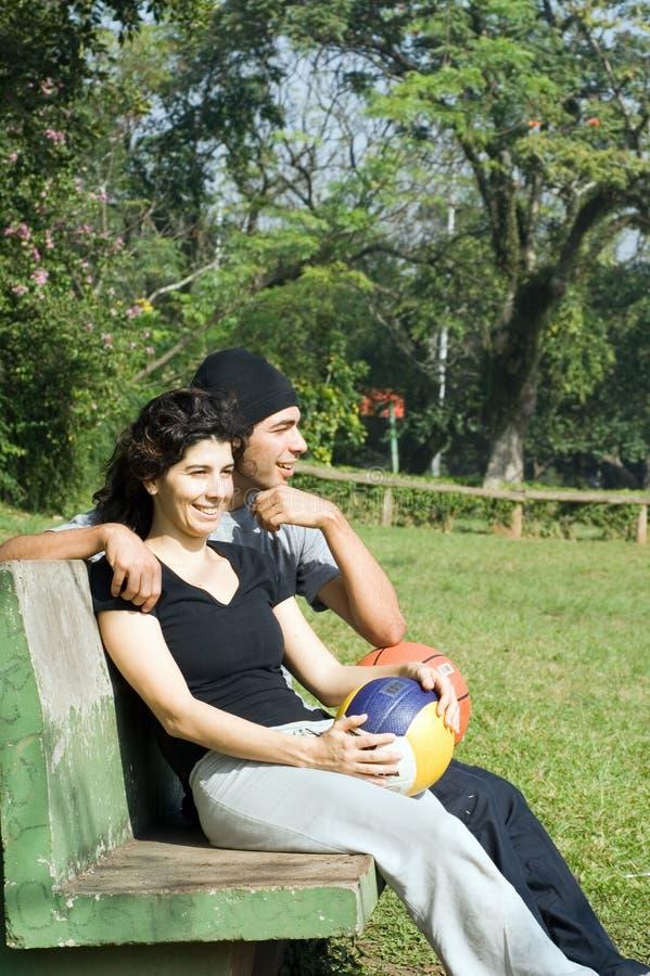 Homem e mulher que sentam-se no voleibol da terra arrendada do banco imagens de stock royalty free