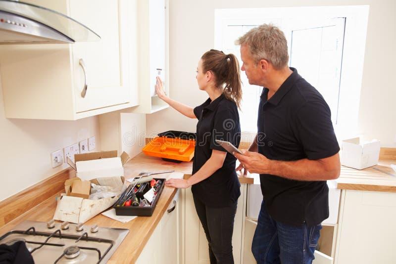 Homem e mulher que trabalham em uma instalação nova da cozinha foto de stock royalty free