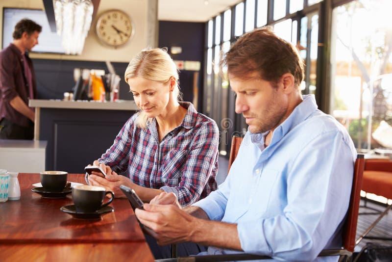 Homem e mulher que usa telefones espertos na cafetaria imagem de stock royalty free