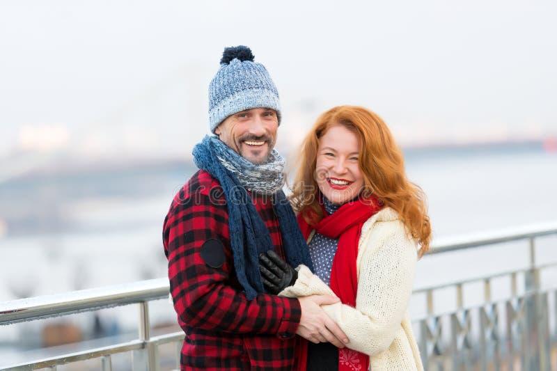 Homem e mulheres da Idade Média que sorriem na rua Mulheres e indivíduo alegres Pares de sorriso na rua no desgaste do inverno fotografia de stock
