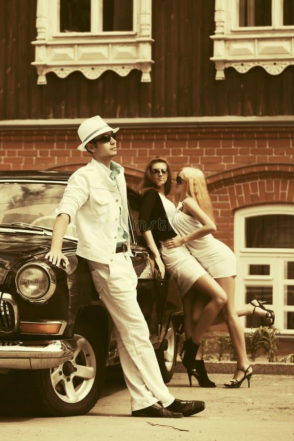 Homem e mulheres novos da forma ao lado do carro do vintage imagens de stock