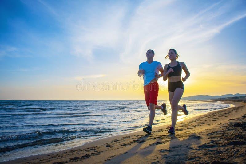 Homem e mulheres que correm na praia tropical no por do sol imagem de stock royalty free