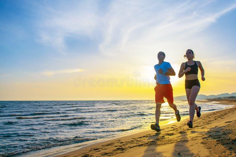Homem e mulheres que correm na praia tropical no por do sol fotografia de stock royalty free