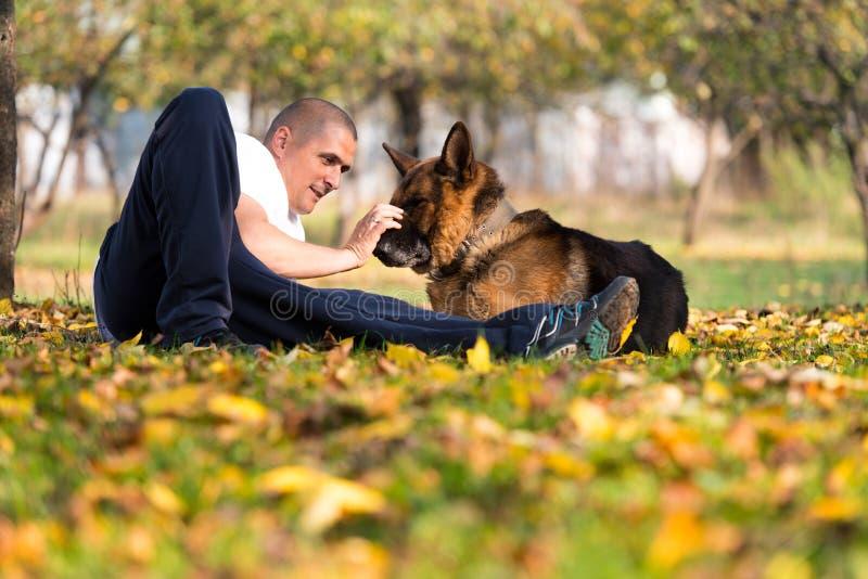 Homem e o seu pastor alemão do cão foto de stock