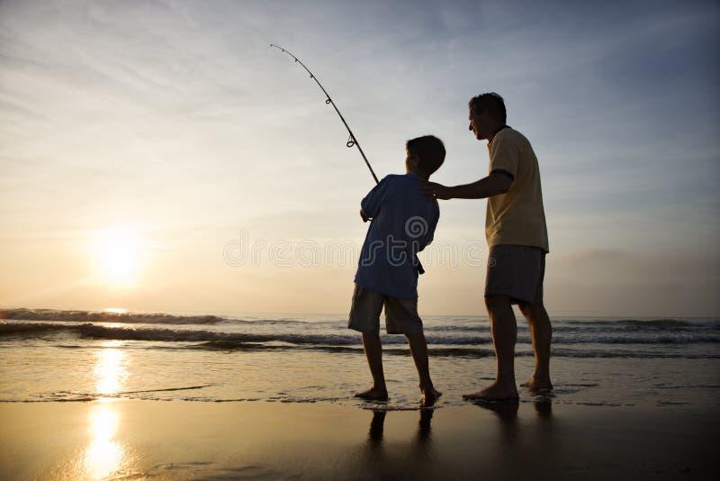 Homem e pesca nova do menino na ressaca foto de stock