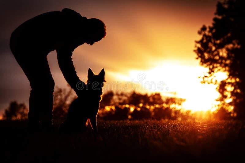 Homem e seu cão que olham a um por do sol ou um nascer do sol, silhueta e luz do sol colorida foto de stock royalty free
