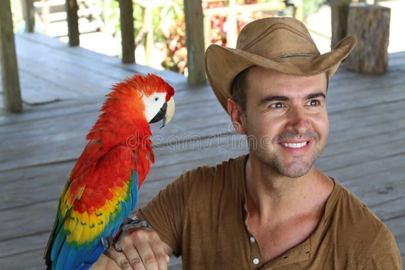 Homem e seu papagaio domesticado fotos de stock