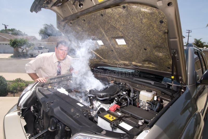 Homem e seu sobre carro heated foto de stock