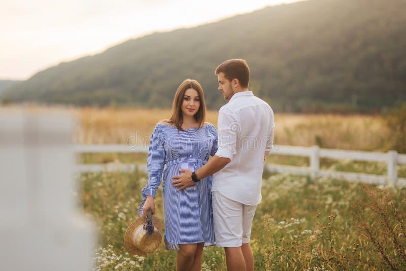 Homem e seu suporte grávido da esposa no campo perto da exploração agrícola e para abraçar-se fotos de stock