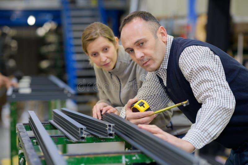 Homem e trabalhadores fêmeas na fábrica dos trabajo em metal foto de stock royalty free