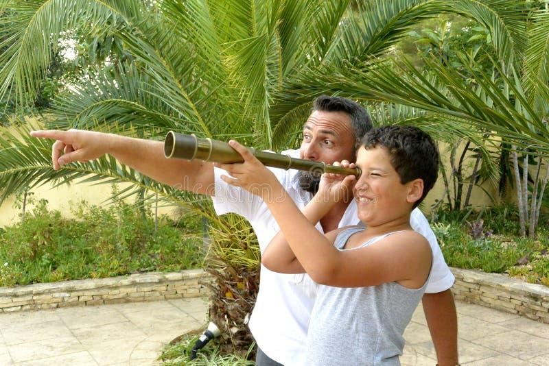 Homem e um menino com telescópio pequeno fotografia de stock