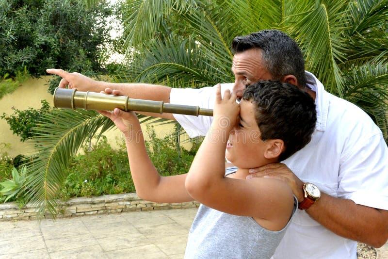 Homem e um menino com telescópio pequeno fotografia de stock royalty free