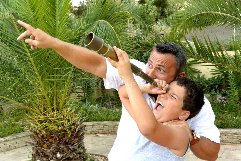 Homem e um menino com telescópio pequeno foto de stock