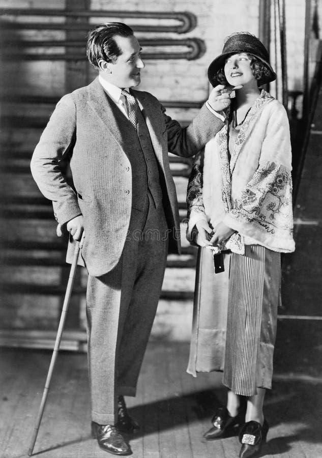 Homem e uma jovem mulher em um chapéu que olha se (todas as pessoas descritas não são umas vivas mais longo e nenhuma propriedade foto de stock