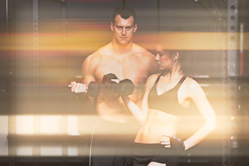 Homem e womanin do treinamento do Barbell um gym fotos de stock