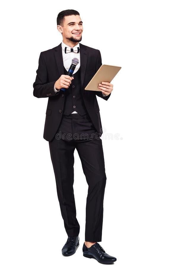Homem elegante à moda em um terno preto com um microfone e uma tabuleta em suas mãos fotografia de stock royalty free