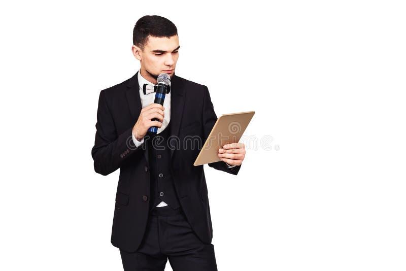 Homem elegante à moda em um terno preto com um microfone e uma tabuleta em suas mãos fotos de stock